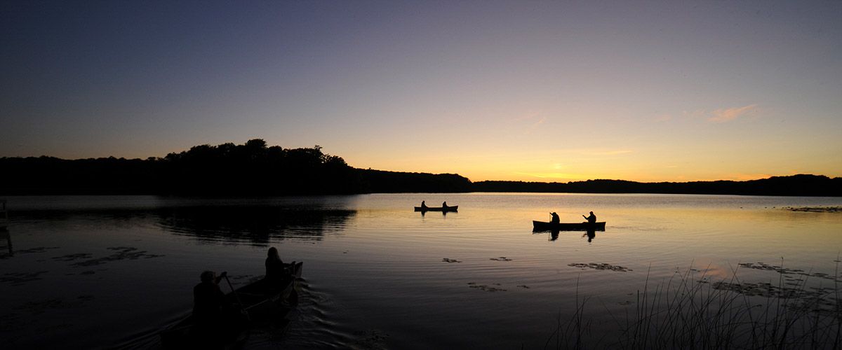 Canoes on the lake at sunset