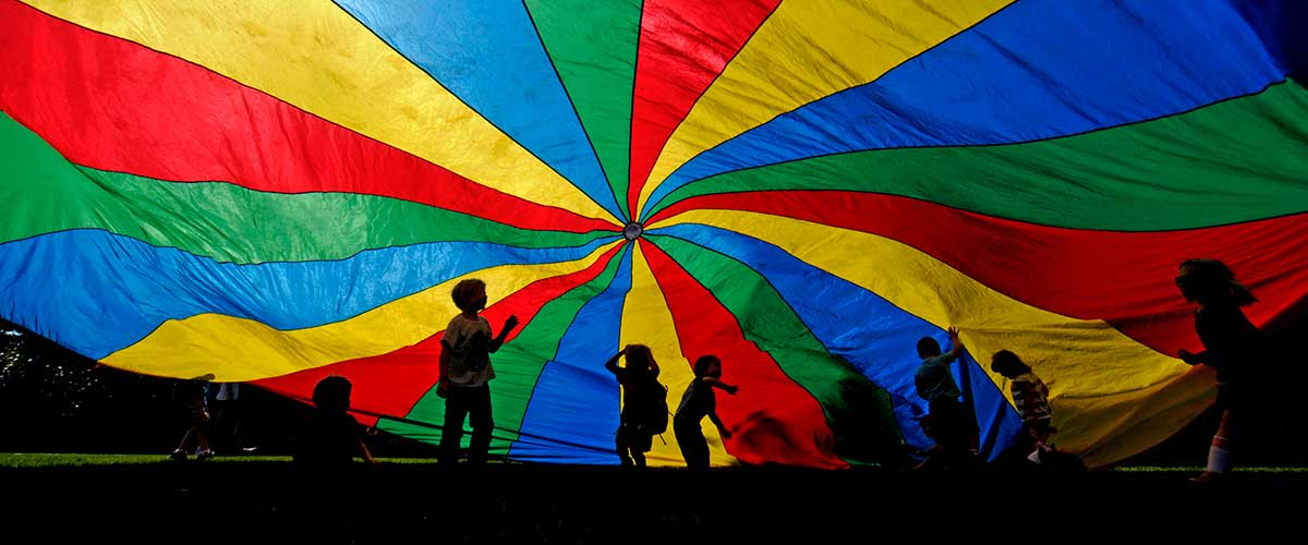 Children playing under multi-color parachute
