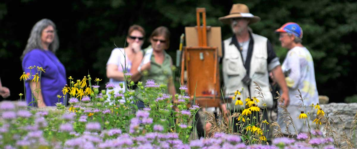 Group of women observe painter behind flowers