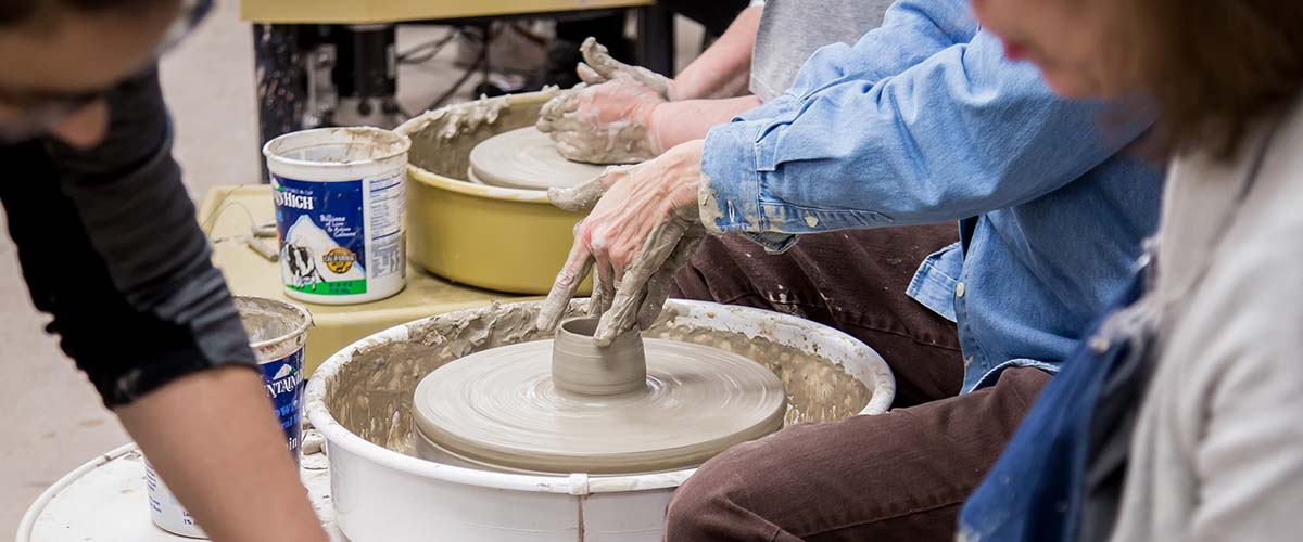 Student forming clay bowl on potters wheel