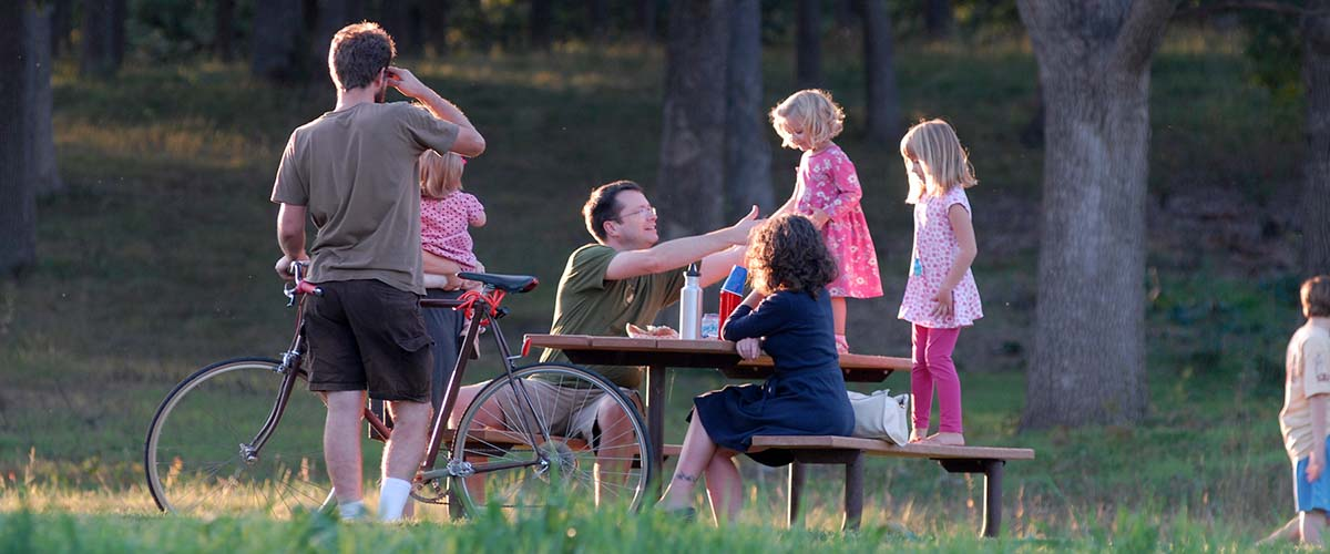 Family and biker at a picnic table